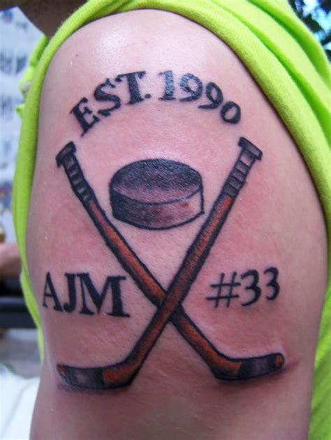 small hockey tattoos crossed hockey sticks on biceps tattoos