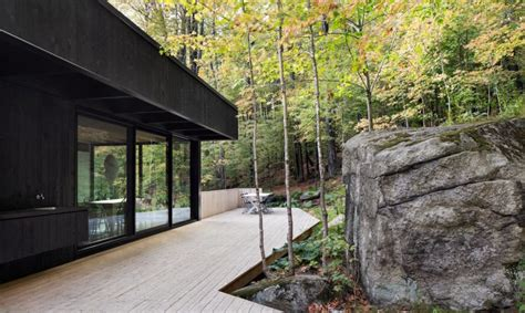 modern charred timber house juts   quebecs forest