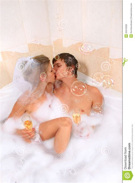 kiss me in the bathroom wedding couple is enjoying a bath with bubbles stock photo