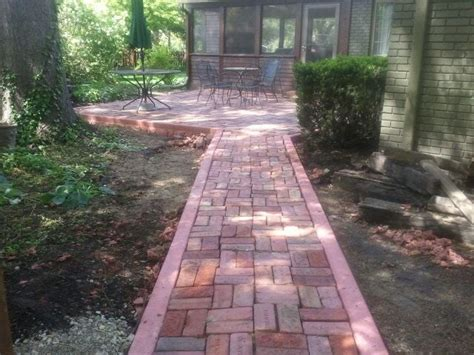 brick patio design install with dyed concrete edging and