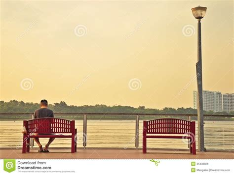 lonely man sitting on a deck with another empty chair