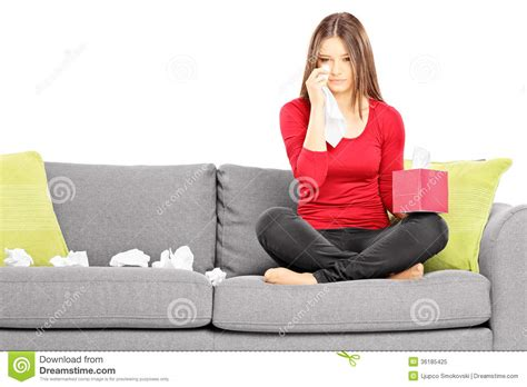 sitting couch sad young female sitting on a couch and wiping her eyes