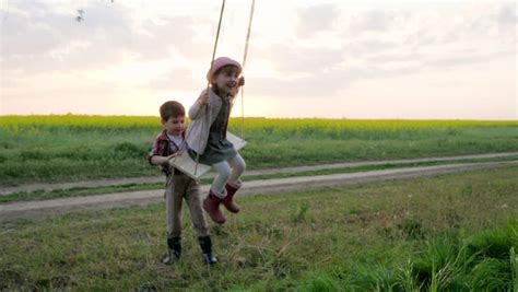 trying swinging mother and two kids standing on hill boy holding long