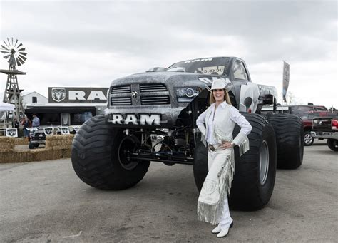 next monster truck show cowgirl dressed in white standing next to monster truck in