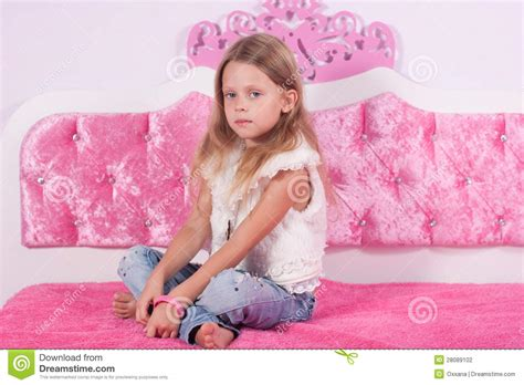 girl sitting on bed little girl sitting on a pink bed stock photography