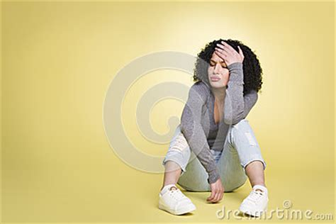 wallpaper of unlucky girl unhappy girl being sad on yellow background stock photo