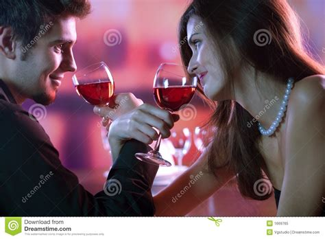 romantic couple drinking wine young couple sharing a glass of red wine in restaurant