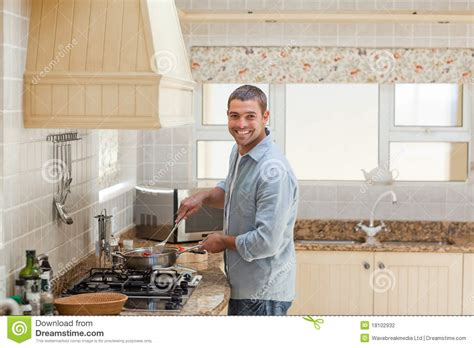 In The Kitchen by Handsome Cooking In The Kitchen Stock Photography