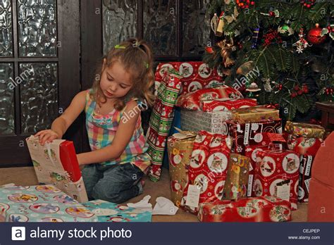 3 year old girl opening christmas presents stock photo