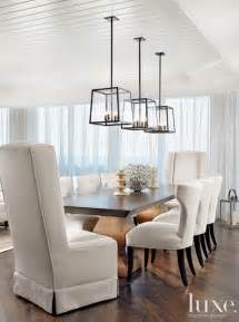 dining light in this stunning dining room three holly hunt light fixtures are suspended over a custom