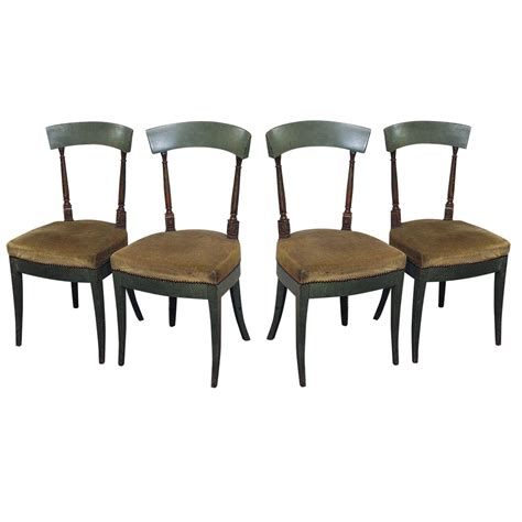 set of four empire painted wood dining chairs upholstered