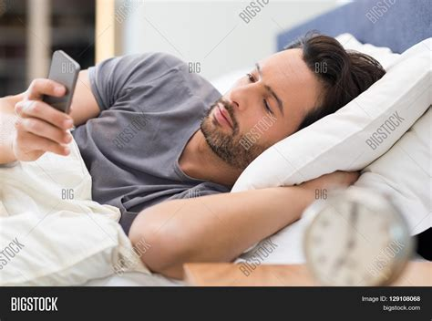 what makes a man good in bed young man checking phone on getting image photo bigstock