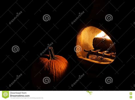 firelit pumpkin on black background royalty free stock