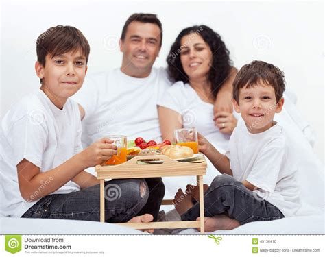 family with two boys breakfast in bed stock photo