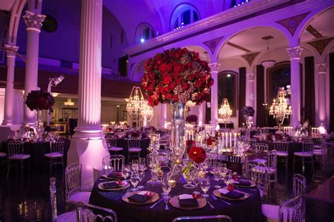 Reception Décor Photos   Tall Red Floral Arrangement on Purple Table   Inside Weddings