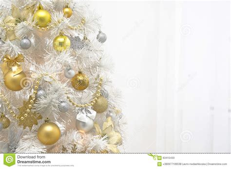 white christmas tree with gold decoration on white