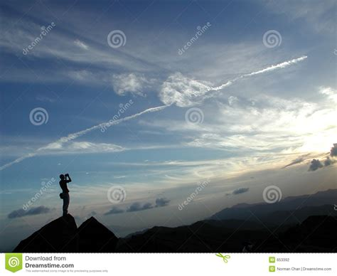 man standing on mountain top a man standing at the top of the mountain stock