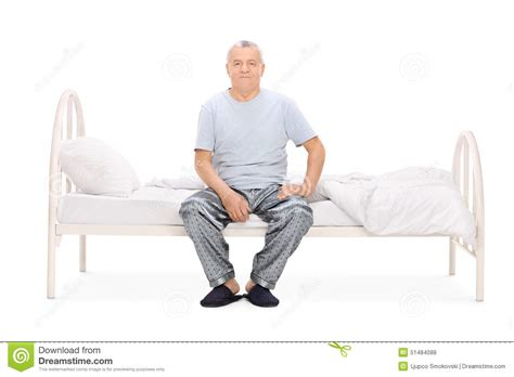 old bed guy senior man in pajamas sitting on a bed stock photo image