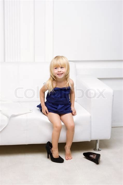 girl sitting on couch little girl sitting on sofa in shoes high heels stock photo