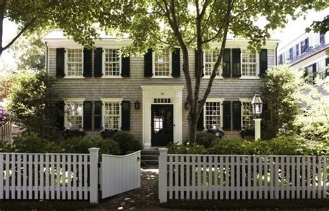 gray colonial house with black shutters and white picket fence gardenista home decor like