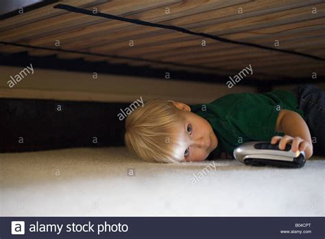 hiding under the bed boy hiding under bed stock photo royalty free image