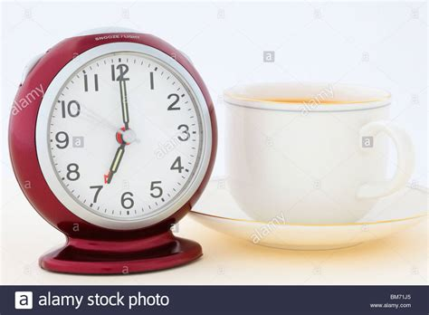 cup of tea by a alarm clock at 7 am in morning just seconds stock photo royalty free image