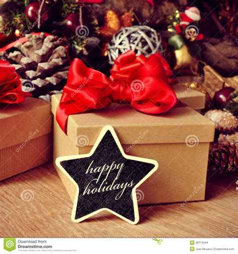 gifts and text happy holidays in a star shaped chalkboard