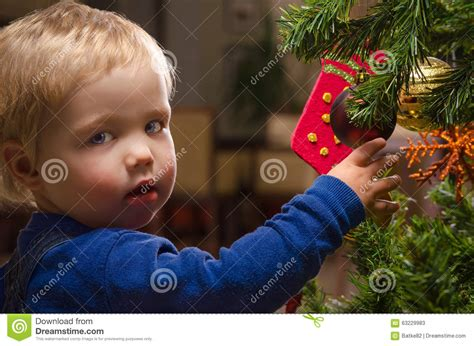 portrait of two year old boy with red curly hair stock two year old boy decorating christmas tree stock photo