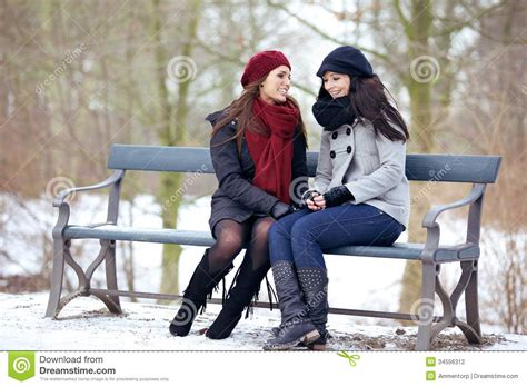 people sitting on a park bench two bestfriends sitting on a park bench stock photography image 34556312