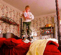 bed gif jumping home alone gif find share on giphy