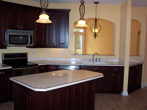 red mahogany kitchen cabinets gray and white marble countertop with cream cabinets photo