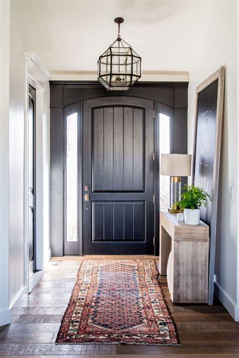 entryway  black front door   kilim rug interiors