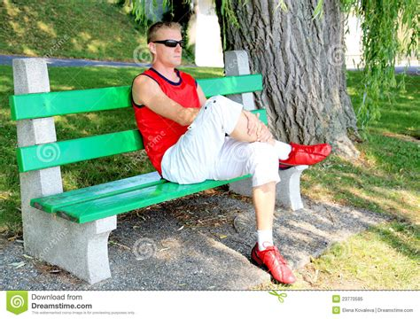 sitting in a park bench young man sitting on a park bench royalty free stock photo