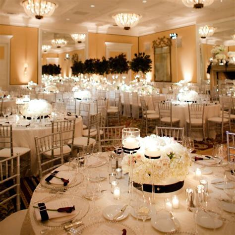 Low, white floral centrepieces and candles decorate round