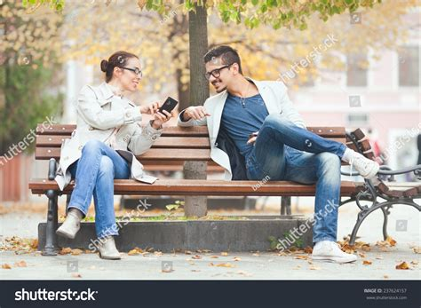 two people sitting on a bench two people sitting on a bench using mobile phone stock