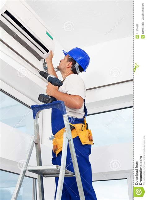 worker mounting air conditioning unit royalty  stock