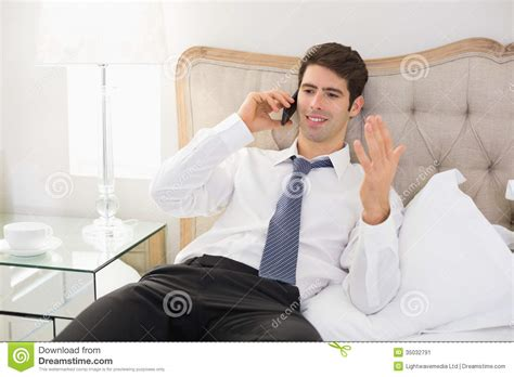 man using cell phone in bed stock images image 33817024 smiling well dressed man using mobile phone in bed stock