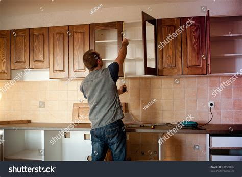 carpenter working on new kitchen cabinets stock photo