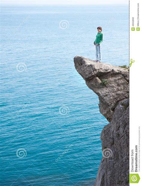 la joven del acantilado b00fbplkwg mujer sola delgada joven que se coloca en el borde del acantilado de la monta 241 a foto de archivo