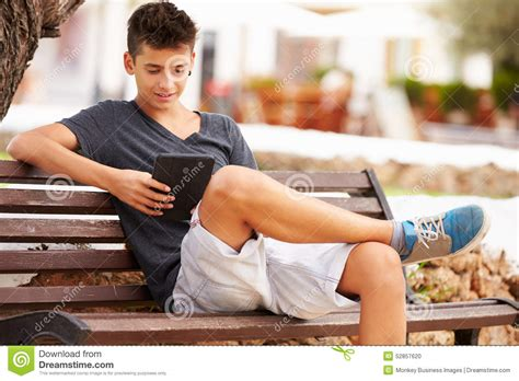 bench boys teenage boy on park bench using digital tablet stock photo