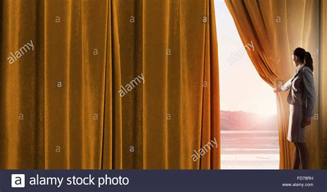 woman opening curtains young woman in business suit opening color curtain of