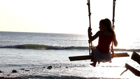 person on swing a girl swings on a tree branch overlooking the sea hd
