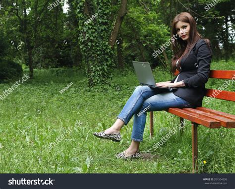 sitting on a park bench song young beautiful brunette girl using notebook stock photo