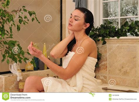 going to the bathroom naked woman using perfum in the bathroom stock photo image