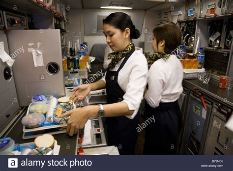 How To Prepare For A Cabin Crew by Member Of Cabin Crew Preparing Meals In The Galley On A