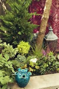 Bohemian garden a hurricane lantern and a turquoise vase amid