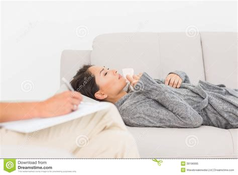 patient couch therapist taking notes on her crying patient on the couch