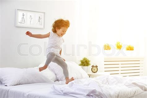 babies jumping on the bed happy child girl having fun jumps and plays bed stock