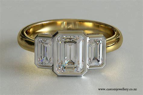 yellow gold emerald cut three bezel set engagement