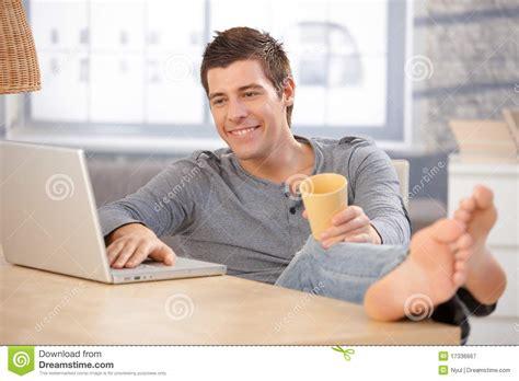 brustmuskeltraining zu hause mann lachender junger mann der zu hause computer verwendet
